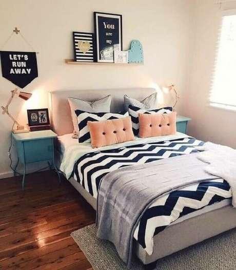 27. Decoração de quarto simples de casal com quadros, almofadas e mesa de cabeceira retrô azul. Fonte: Pinterest