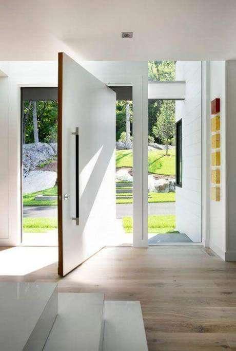 7. A porta pivotante branca é perfeita para decorar a entrada de casa – Foto LDA Arquitecture e Interiors