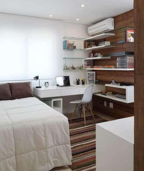 17. Home office no quarto decorado com tapete listrado e bancada suspensa branca. Foto: Casa de Valentina