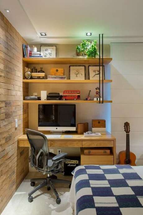 18. Home office no quarto decorado com parede de tijolinho e escrivaninha de madeira. Foto: Casa de Valentina