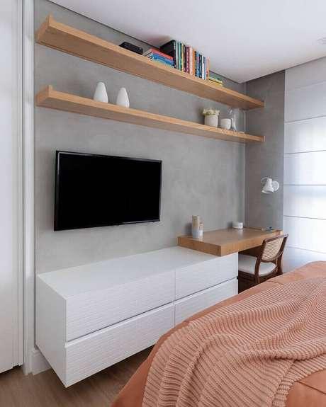 56. Bancada de madeira para home office no quarto de casal decorado com parede de cimento queimado. Foto: Duda Senna