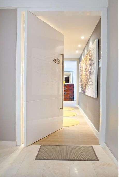 21. Porta pivotante branca e grande para entrada de apartamento moderno – Foto AD&E