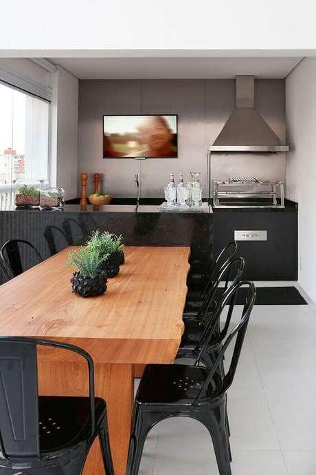 18. Mesa de madeira para área externa com cadeiras pretas industriais – Foto Casa de Valentina