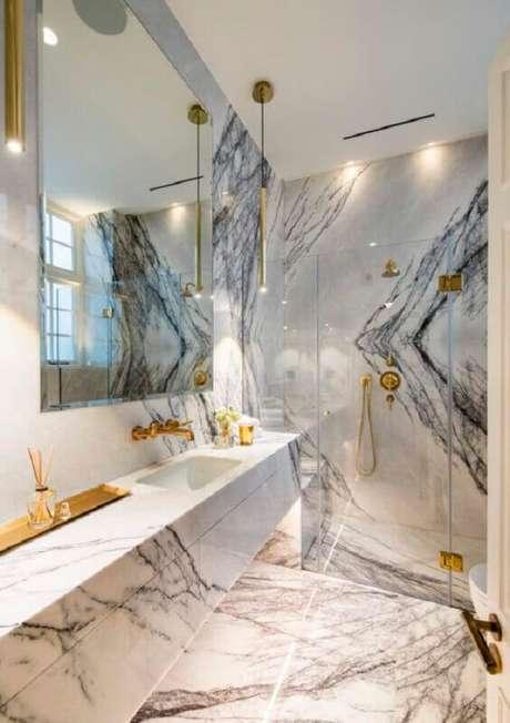 21. Bancada de mármore para banheiro sofisticado decorado com detalhes em dourado – Foto One Kindesign