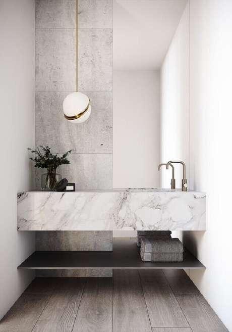 54. Decoração sofisticada com luminária moderna e bancada de mármore branco para banheiro – Foto Behance