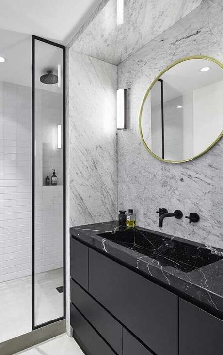 30. Banheiro sofisticado decorado com espelho redondo e bancada de mármore preto – Foto Behance