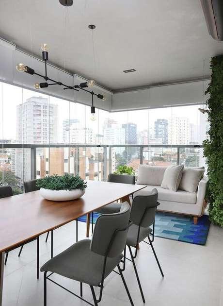 28. Varanda de apartamento com mesa de madeira e cadeiras cinza – Foto Casa e Jardim
