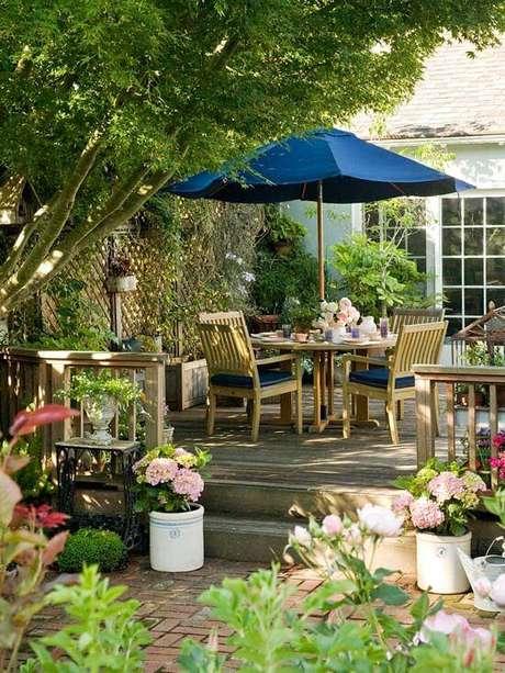 6. Jardim com mesa para área externa e guarda sol azul – Foto Better Homes and Gardens