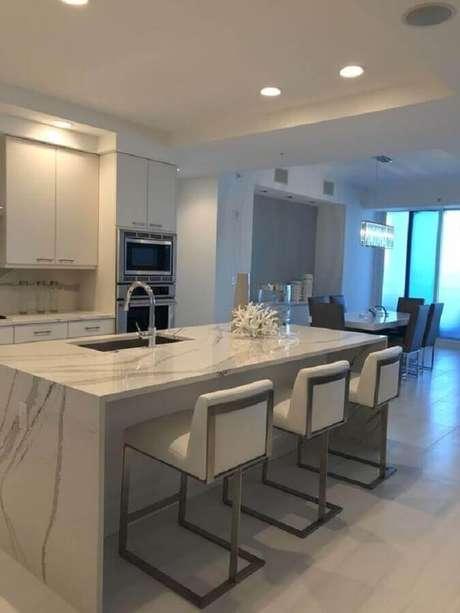 33. Decoração clean com bancada de mármore para cozinha branca com ilha – Foto Real Simple