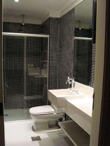 34. Banheiro com pastilha preta e chuveiro cromado no teto. Projeto por Daniella Lima