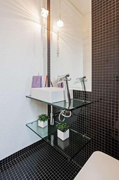 14. Na decoração desse lavabo piso e parede recebem acabamento em pastilha preta. Projeto por Patrícia Azoni