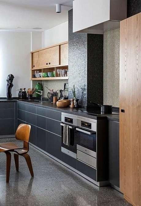 26. Cozinha planejada e decorada com pastilha preta e armário aéreo de madeira. Fonte: Archilovers