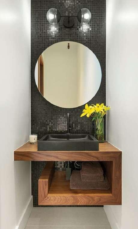 7. Parede estreita revestida com pastilha preta e espelho redondo. Fonte: Arkpad