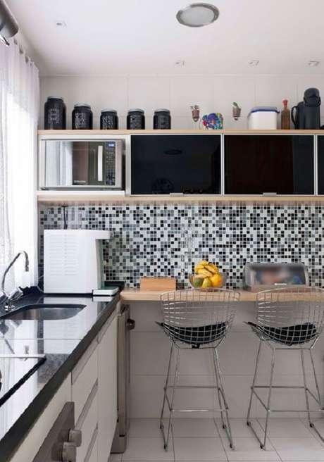 29. Cozinha com pastilha preta e branca, bancada de madeira e cadeiras cromadas. Fonte: Fashionismo