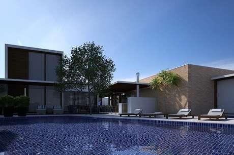 13. Espreguiçadeiras de madeira e azulejo azul para piscina decoram a área de lazer do terreno. Projeto por Olegário de Sá & Gilberto Cioni