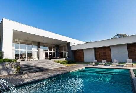 32. O deck de madeira e o azulejo azul para piscina formam uma linda composição na área externa. Projeto por Leonardo Muller