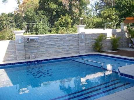 26. O azulejo para piscina em tons de azul foi usado em conjunto com o azulejo branco. Projeto por Alessanara Maioli