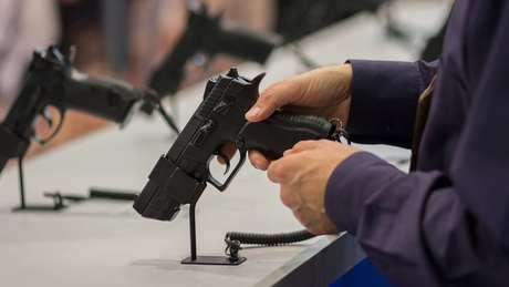 Pessoa segurando arma em mostruário em uma loja