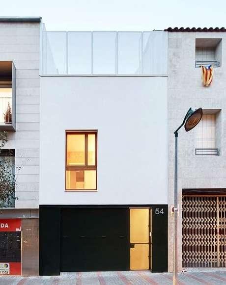 14. Portão de ferro preto em casa com fachada branca minimalista. Foto de Jose Hevia
