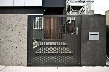 40. Portão de ferro cinza vazado combinando com projeto de casa moderna com muro preto. Foto de Pierre Le Roux Design