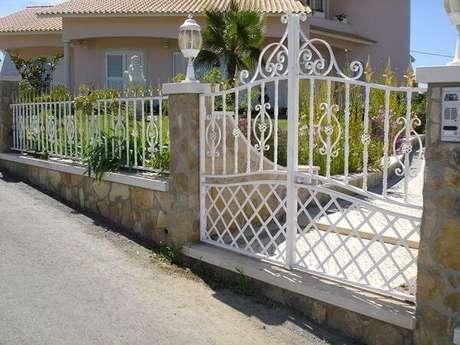 23. Portão de ferro baixo e bem trabalhado em casa com jardim na frente. Foto de Cell Code