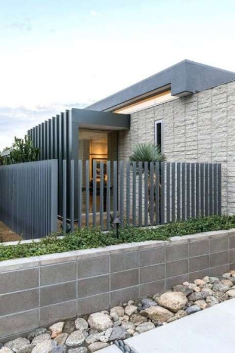 16. Portão de ferro cinza em fachada de casa moderna. Foto de News Ease