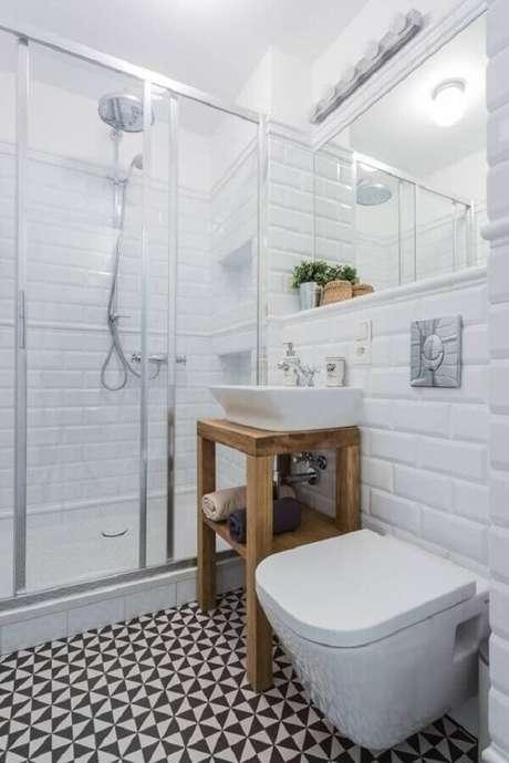 7. Azulejo de banheiro simples decorado com piso preto e branco e armário pequeno de madeira. Foto: Homify