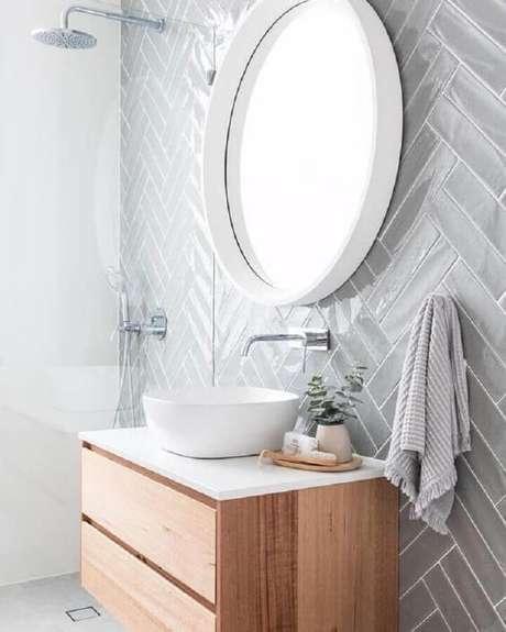 41. Decoração com espelho redondo e azulejo de banheiro cinza claro. Foto: Pinterest