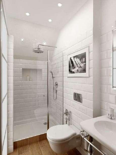 53. Azulejo de banheiro pequeno decorado todo branco com piso amadeirado. Foto: Arquitrecos