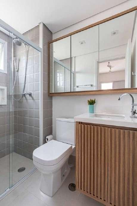 40. Decoração com gabinete de madeira e azulejo para box de banheiro cinza. Foto: Apto 41