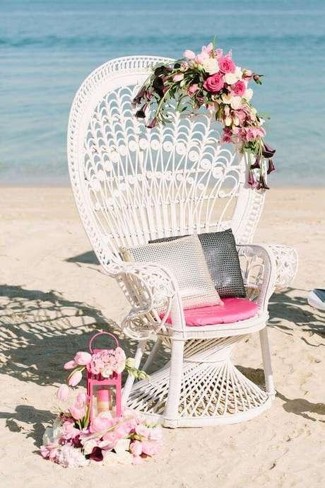 24. Poltrona de vime branca na praia decorada com flores cor de rosa – Foto Burnetts boards