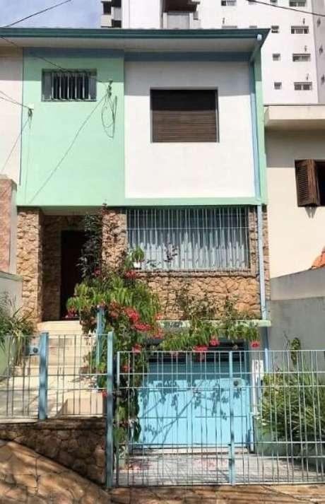 41. Portão de ferro azul vazado em casa grande e colorida. Foto de Pinosy