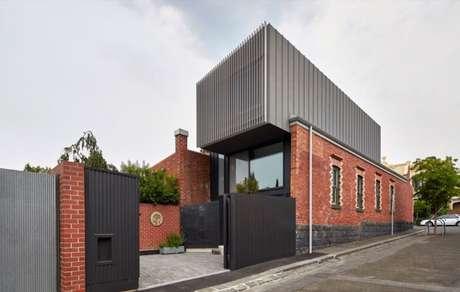 32. Portão de ferro preto em casa grande com muro de tijolinhos. Foto de Home DSGN