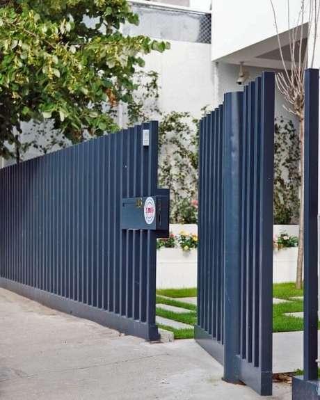 7. Portão de ferro azul com porta pivotante embutida. Foto de Home DSGN