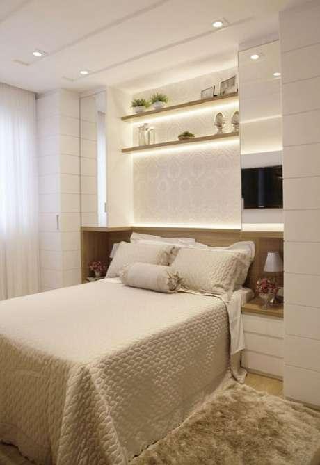 9. A iluminação traz um toque especial para essa cama com guarda-roupa embutido. Fonte: Suelen Kuss Arquitetura