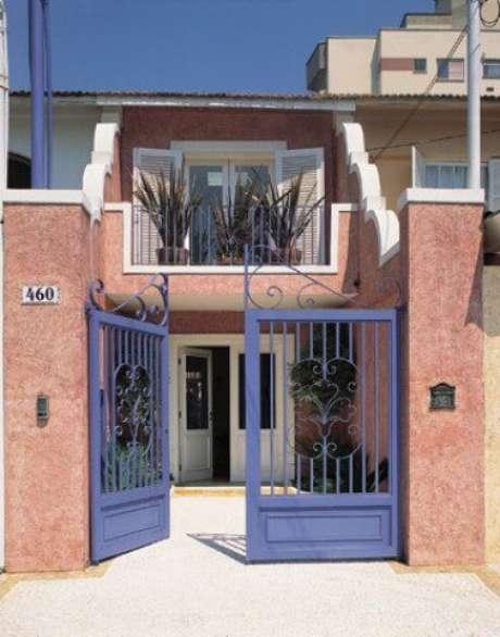 27. Portão de ferro roxo em casa com fachada em tom rosa. Foto de EMD Battery