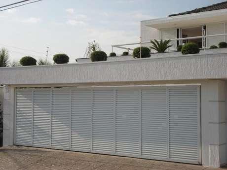 57. Portão de ferro amplo combinando com a fachada clara da casa. Foto de Tampa Roofer