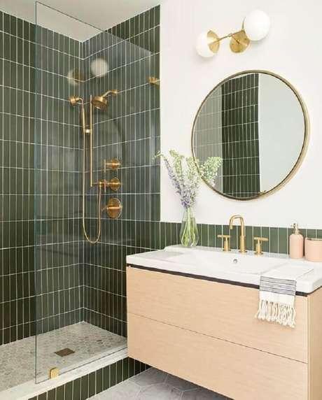 8. Azulejo para parede de banheiro verde decorado com gabinete suspenso de madeira clara. Foto: Casa de Valentina