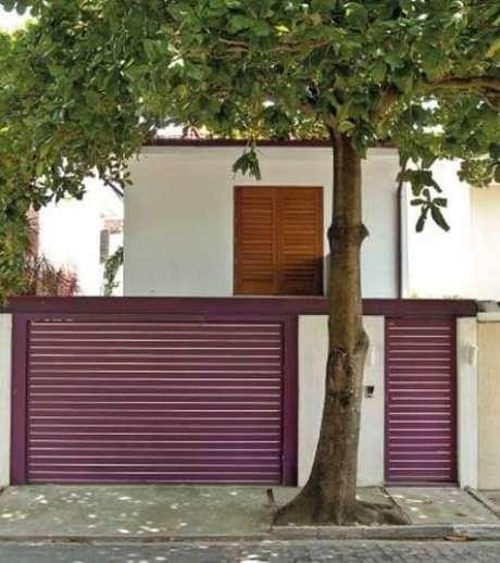33. Portão de ferro em tom de roxo claro combinando com o telhado da casa. Foto de Jardins Maravilhosos