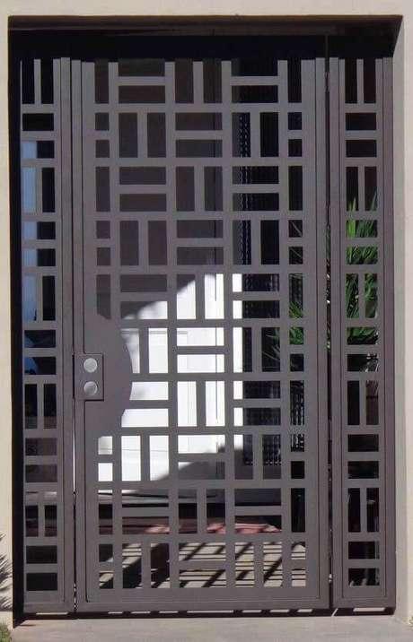 26. Portão de ferro preto com padrão geométrico. Foto de Dekostile