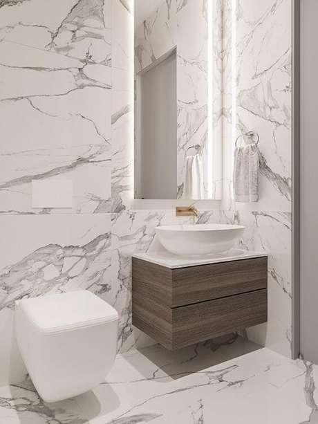 50. Banheiro com revestimento marmorizado cinza e móveis chiques de madeira – Foto Behance