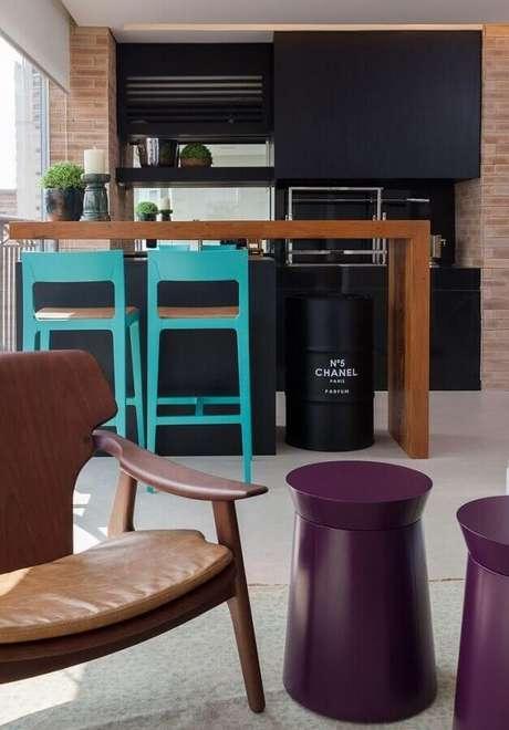 16. Varanda gourmet moderna decorada com banquetas para bancada coloridas. Foto: Casa de Valentina