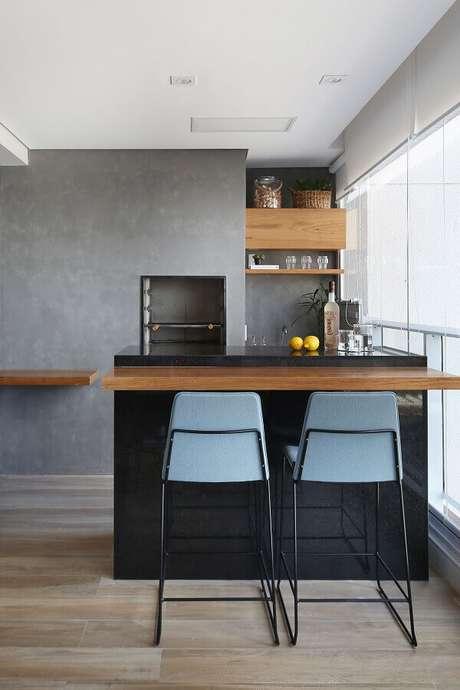 9. Banquetas para bancada com encosto para varanda gourmet moderna decorada com parede de cimento queimado. Foto: Revista Morar Bem