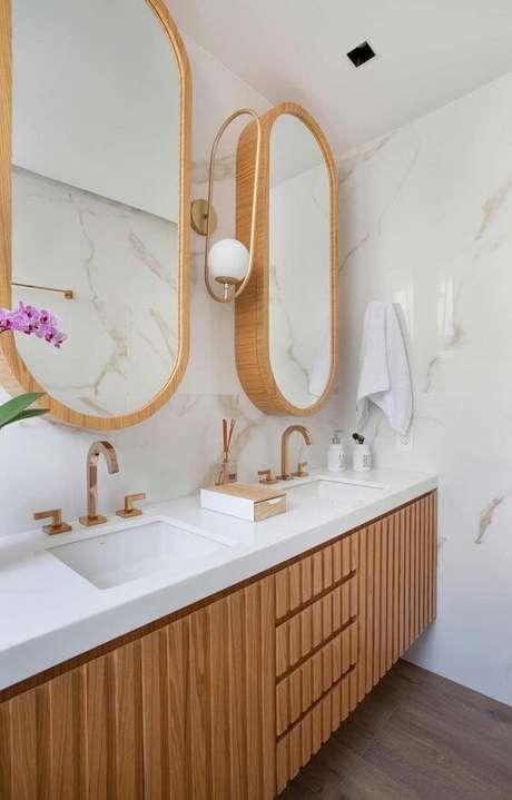 52. Banheiro com revestimento marmorizado e armários de madeira -Foto Casa de Valentina