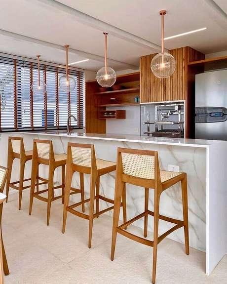 1. Área gourmet decorada com churrasqueira e banquetas para bancada de madeira. Foto: Jeito de Casa