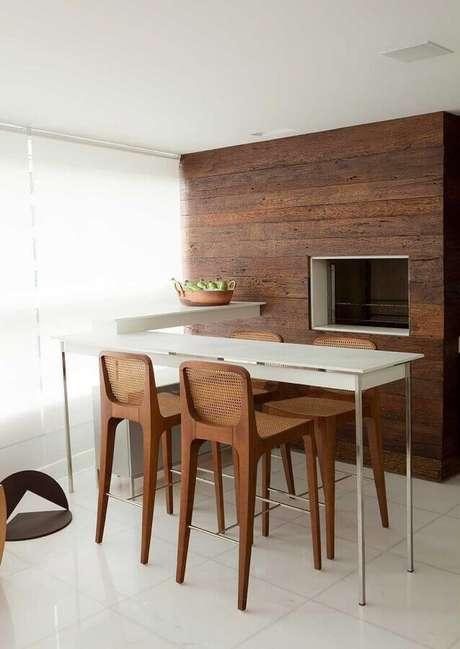 24. Decoração minimalista com banquetas para bancada de madeira em varanda gourmet com churrasqueira. Foto: Luiz Fábio Rezende de Araújo