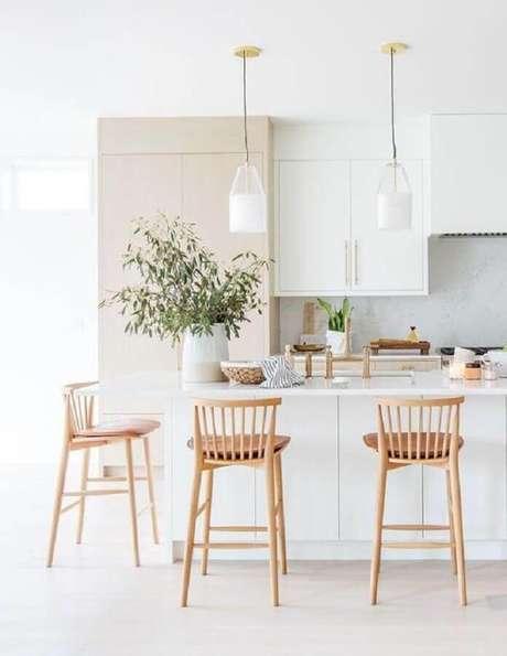 51. Cozinha branca clean decorada com banquetas para bancada de madeira. Foto: Apartment Therapy