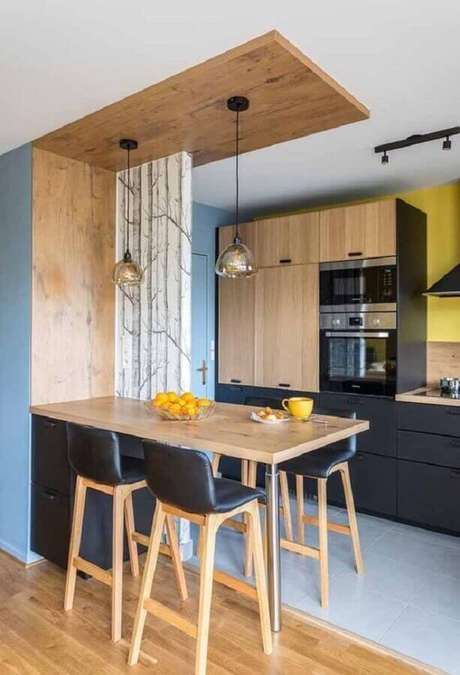 21. Decoração simples com banquetas para bancada de cozinha com armários pretos. Foto: Homedit