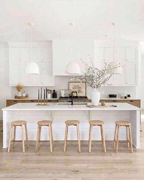 50. Cozinha branca com ilha decorada com banquetas para bancada de madeira. Foto: Apartment Therapy