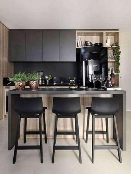 35. Decoração com banquetas para bancada de cozinha preta com detalhes em madeira. Foto: Pinterest